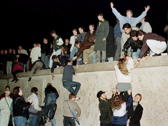east-german-citizens-climb-the-berlin-wall-at-the-brandenburg-gate-as-they-celebrate-the-opening-of-the-east-german-border-november-10-1989-reutersfile
