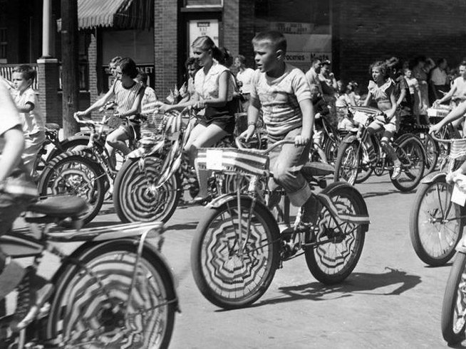 1953 Children with decorated bikes ride in the 4th of July parade.